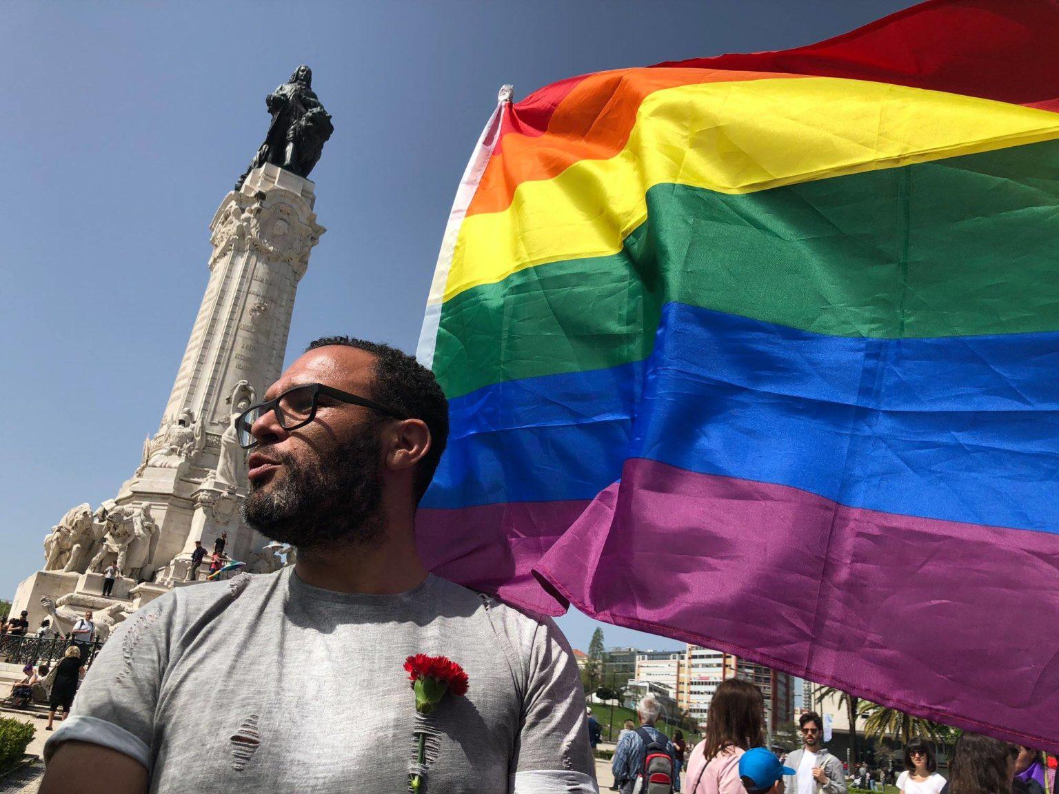 Homem negro numa manifestação do 25 de abril, em Lisboa, envergando uma bandeira LGBTI